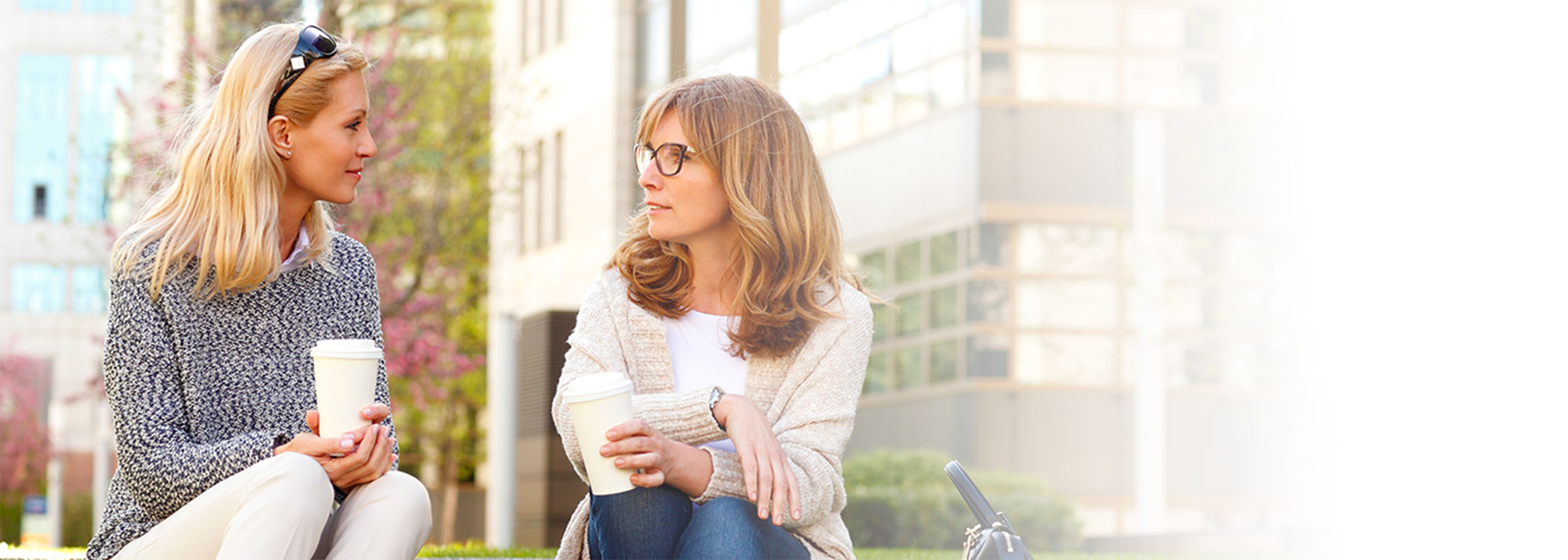 Two women sitting in a city, drinking coffee.